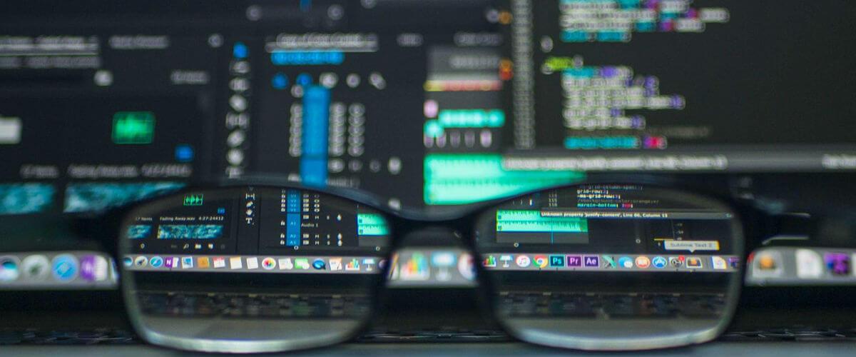 Un bureau avec des lunettes et des données informatiques en arrière-plan